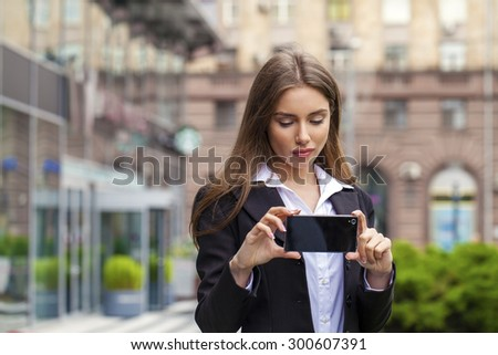 Young beautiful business woman photographed on a cell phone in a summer street
