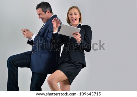 Young beautiful business woman playing with a tablet and male colleague playing with a phone - stock photo