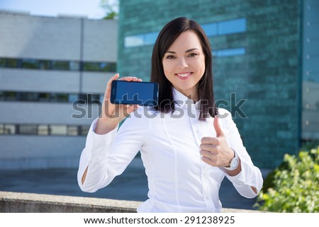 young beautiful business woman showing smartphone with blank screen - stock photo