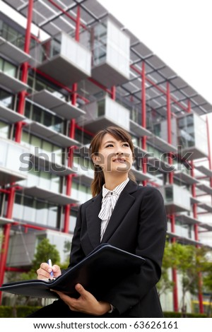 young beautiful business woman Sitting in front of the modern building - stock photo