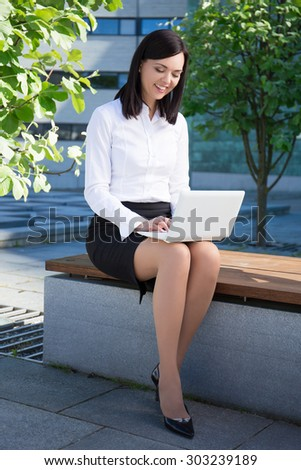 young beautiful business woman sitting with laptop in city park - stock photo