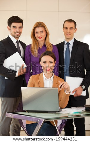 Young beautiful business woman smiling with a laptop in front of her and three colleagues business people in the back - stock photo