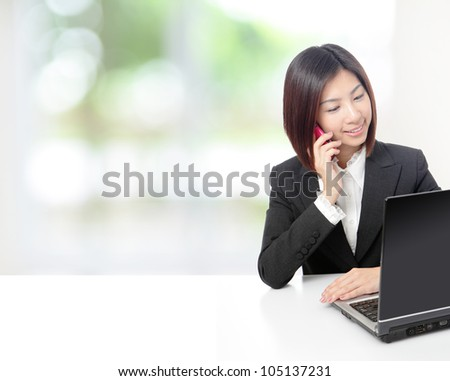 Young beautiful business woman speaking mobile phone and using computer at office with nature green window, model is a asian beauty - stock photo
