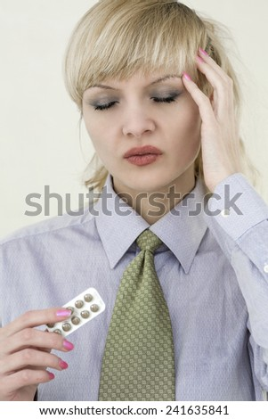 Young beautiful business woman with migraine and pills - stock photo