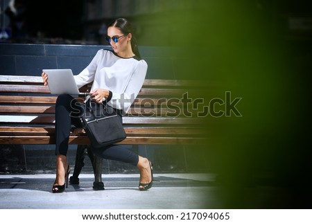 Young beautiful business woman working on a laptop - stock photo