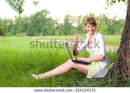 Young beautiful business woman working on laptop in the park