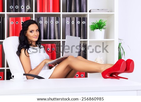 young beautiful businesswoman at office with laptop - stock photo