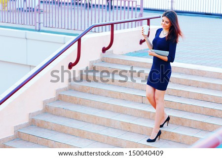 Young beautiful businesswoman going down the stairs with coffee and tablet computer - stock photo