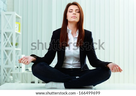 Young beautiful businesswoman meditates on the table in office - stock photo