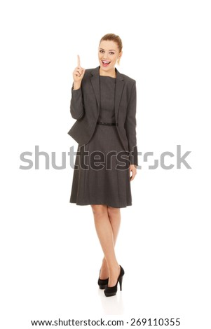 Young beautiful businesswoman pointing up.
