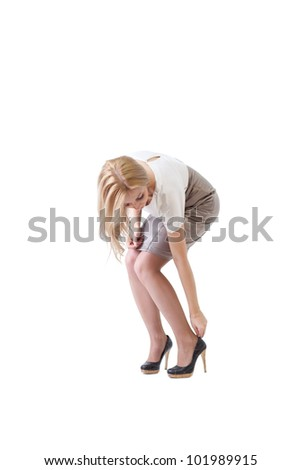 Young beautiful businesswoman putting on  high heels.  Isolated on white background. - stock photo