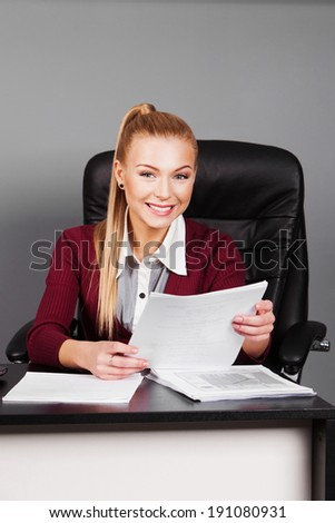 Young beautiful businesswoman sitting at workplace and reading paper in office - stock photo
