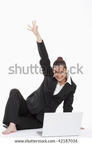 young beautiful businesswoman sitting in front of her laptop cheering