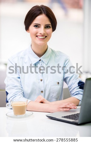 Young beautiful businesswoman  sitting in urban cafe and using laptop. - stock photo