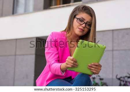Young beautiful businesswoman sitting on a bench with green tablet