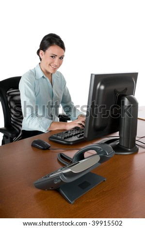 Young, beautiful businesswoman typing at the computer at work, happy and smiling, isolated on white background - stock photo