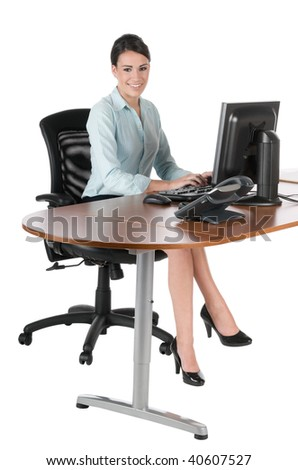 Young, beautiful businesswoman typing at the computer, sitting down at desk, happy and smiling, isolated on white background