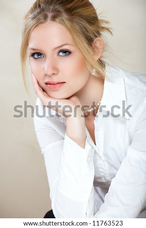 Young beautiful businesswoman with blond hair and blue eyes in white shirt - stock photo