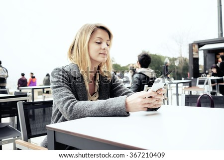 young beautiful businesswoman with blonde hair using smart-phone outside coffee-shop. attractive girl chatting with her friends - stock photo