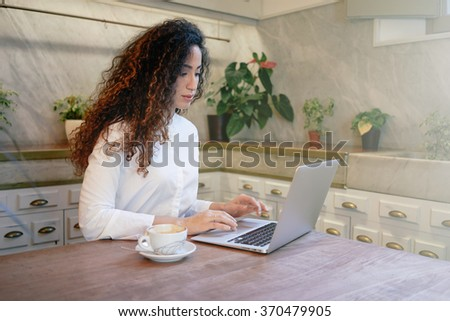young beautiful businesswoman with long curly hair working in a coffee-shop with her laptop computer. attractive student surfing information for a thesis on the Internet - stock photo