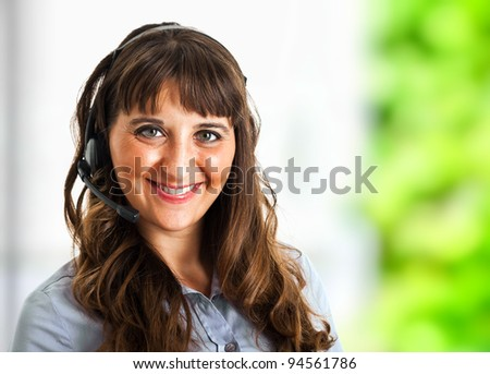Young beautiful call center female operator in her office - stock photo