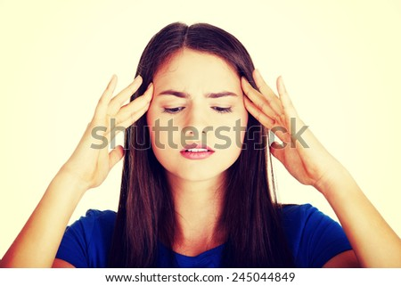 Young beautiful casual woman is touching her temples.  - stock photo
