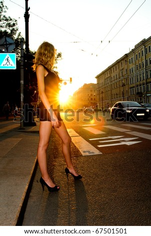 young beautiful caucasian blond woman crossing the street in sunset lightning - stock photo