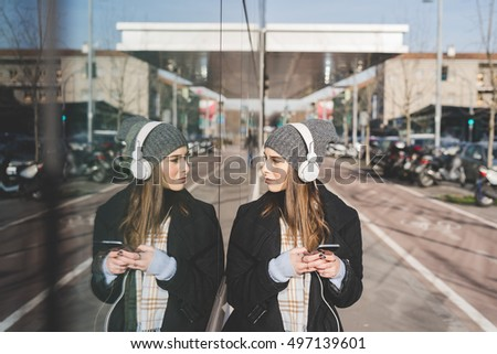 Young beautiful caucasian blonde girl listening music with headphones and smart phone hand hold, reflecting on a mirror window - music, technology, relaxing concept