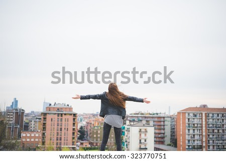 Young beautiful caucasian blonde girl with arms wide open with city on background, feeling free in the suburbs - freedom, satisfaction, future, girl power, emancipation concept. View from back - stock photo