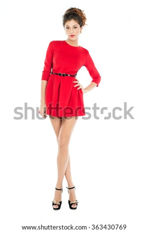 Young beautiful caucasian brunette in fashion red gown posing on white background