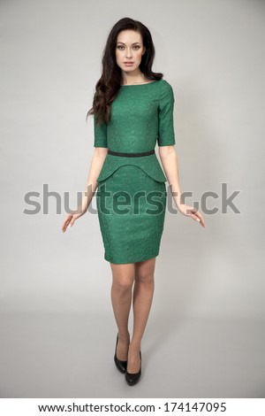 Young beautiful caucasian brunette in green dress posing on grey background  - stock photo
