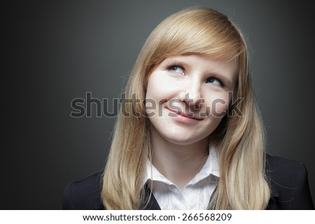Young beautiful Caucasian business woman with blue eyes close up studio shot on gray background. Looking up slightly smiling.  - stock photo