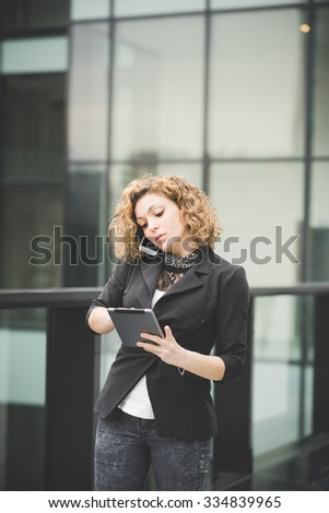 Young beautiful caucasian contemporary businesswoman talking smartphone while using a tablet looking down the screen- technology, network, business, finance concepts - stock photo