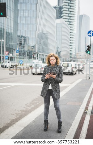 Young beautiful caucasian contemporary businesswoman walking through the streets of the city using a tablet looking down the screen - technology, network, business, finance concepts - stock photo