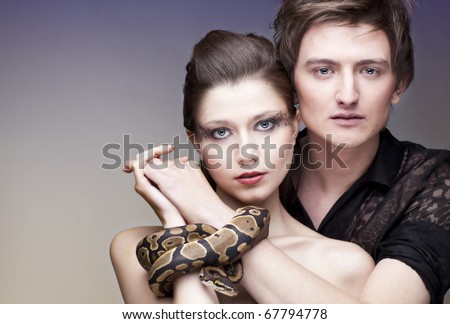 Young, beautiful caucasian couple with their hands connected with gorgeous royal python; a lot of copyspace available - stock photo