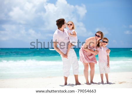 Young beautiful Caucasian family on Caribbean beach vacation - stock photo