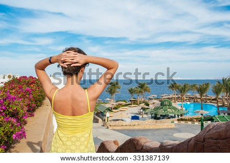 young beautiful caucasian female in vibrant yellow dress looks at the sea. - stock photo
