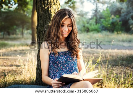 young beautiful caucasian female reading book in park