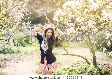 Young beautiful caucasian girl in a blossoming spring magnolia garden. The girl in the garden morning. Boho style. Portrait. The girl in the hat, necklace and earrings. - stock photo