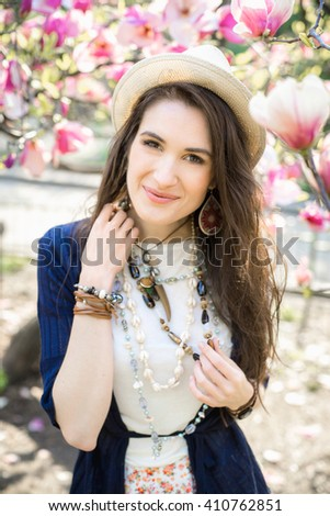 Young beautiful caucasian girl in a blossoming spring magnolia garden. The girl in the garden morning. Boho style. Portrait, close-up. The girl in the hat, necklace and earrings. - stock photo