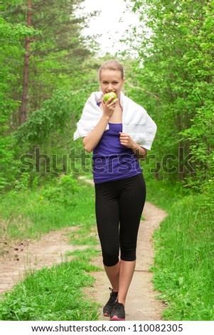 Young beautiful caucasian woman after sport workout eating apple outdoors - stock photo