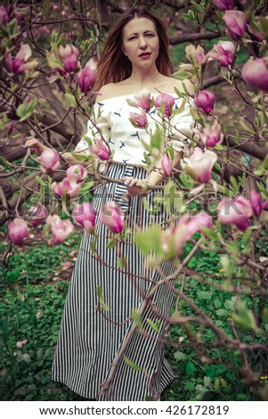Young beautiful caucasian woman in blooming spring garden of magnolias . The girl in the garden on a cloudy day . High-fashion. - stock photo