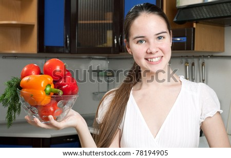 young beautiful caucasian woman in the kitchen with vegetable