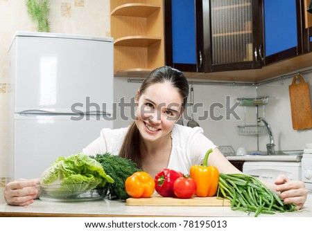 young beautiful caucasian woman in the kitchen with vegetable - stock photo
