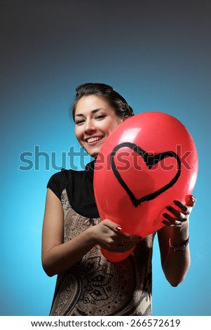 Young beautiful Caucasian woman is holding red baloon with painted heart. Smiling and looking at camera. - stock photo