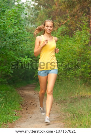Young beautiful caucasian woman jogging in summer park