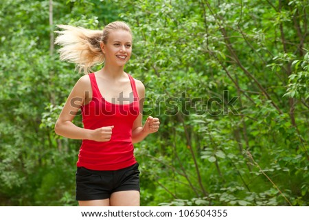 Young beautiful caucasian woman jogging in summer park. Woman in sport outdoors - stock photo