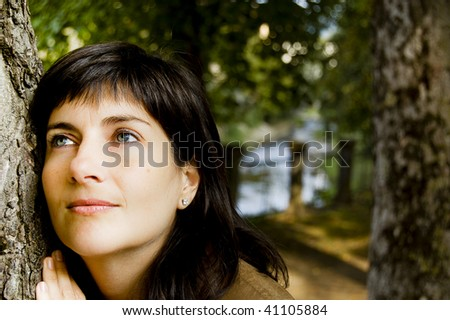 Young beautiful caucasian woman laying her head on a tree