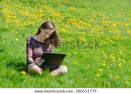 Young beautiful caucasian woman sitting on a sunlit meadow and working on laptop. - stock photo