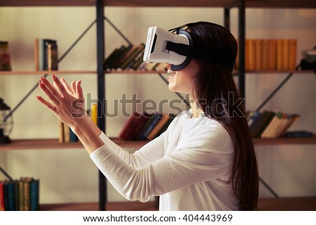 Young beautiful Caucasian woman trying to catch something using modern virtual reality headset glasses - stock photo